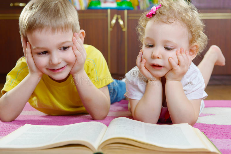 cute-little-brother-sister-reading-book-floor-home-30108197